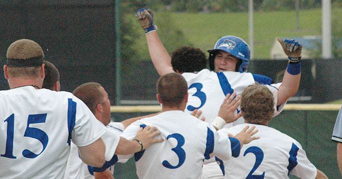 Russ Morse (facing) is mobbed by teammates after his game-ending single