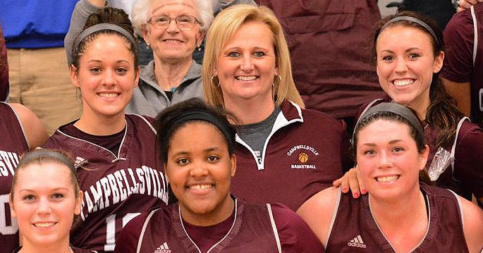 Campbellsville women's basketball coach Ginger Colvin is surrounded by her team after winning her 200th career game.